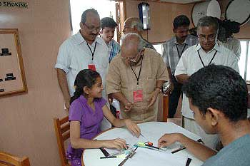 Yesudasan speaking to a cartoon workshop participant during 'Yesudasan: Celebrating 50 Years of Responsible Cartooning', at Kochi, Kerala on May 19, 2005. Photo: Vipin Chandran, The Hindu.