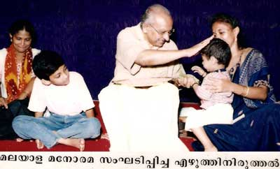 Yesudasan blesses a child during the 'Harishri' ceremony organised by Malayala Manorama at Kochi.
